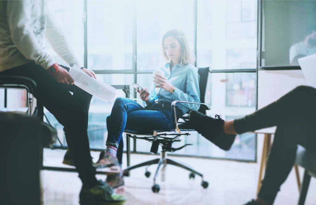Eine Frau mit Smartphone in der Hand in einem Meeting mit Kollegen.